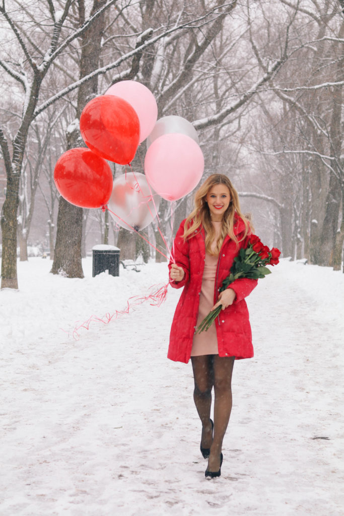 Lifestyle blogger Leigha Gardner of The Lilac Press in a blush pink Asos dress, red down puffer jacket heading down Commonweath Ave with Valentine's Day balloons and roses in tow.