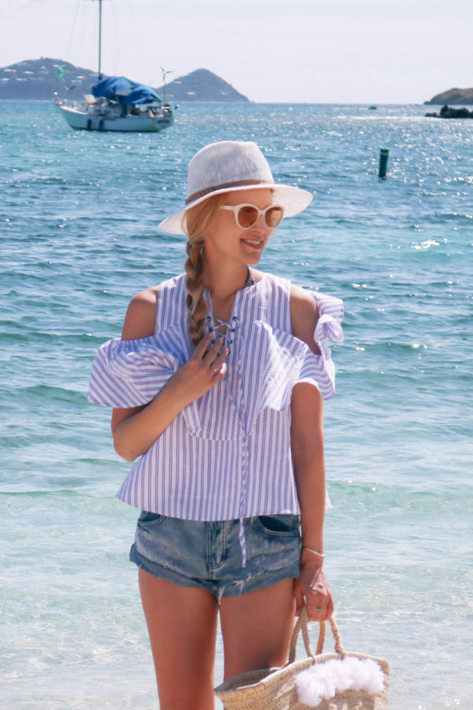 Lifestyle blogger, Leigha Gardner, of The Lilac Press walking on the beach in St. Thomas wearing a striped cold shoulder blouse and denim cutoffs.