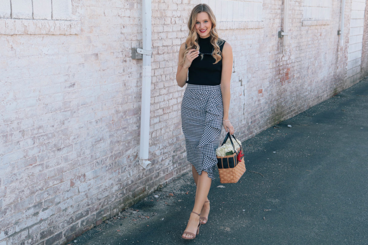 Style blogger Leigha Gardner, of The Lilac Press, wearing a navy gingham skirt, black tank and a basket tote with a bright red bow (sharing tips on mixing black and navy).