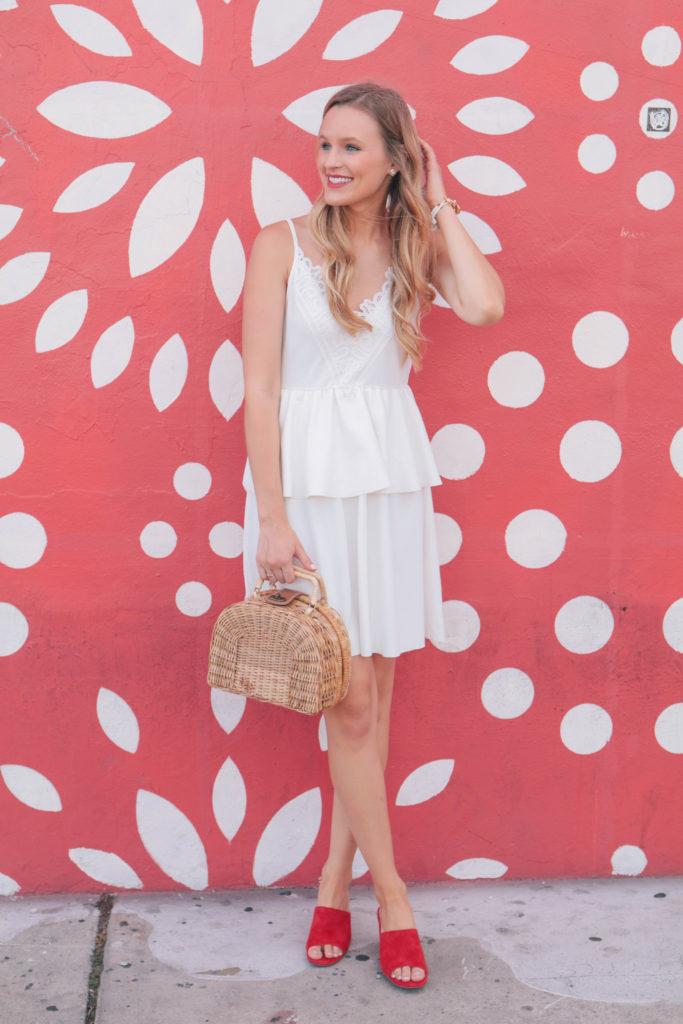 Fashion blogger, Leigha Gardner, of The Lilac Press exploring the colorful Wynwood district of Miami wearing a little white dress and red suede mules.