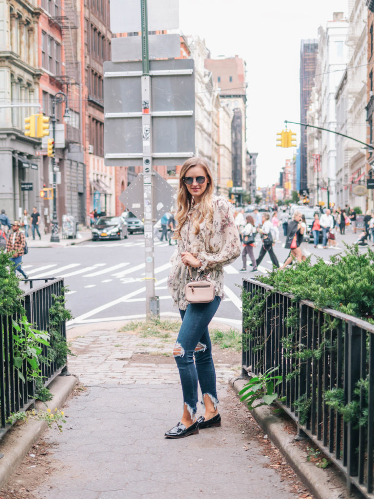 Fashion blogger, Leigha Gardner, wearing Zimmermann maples frill top, L'Agence distressed jeans, Milly crossbody and Chanel sunglasses during fashion week in NYC.