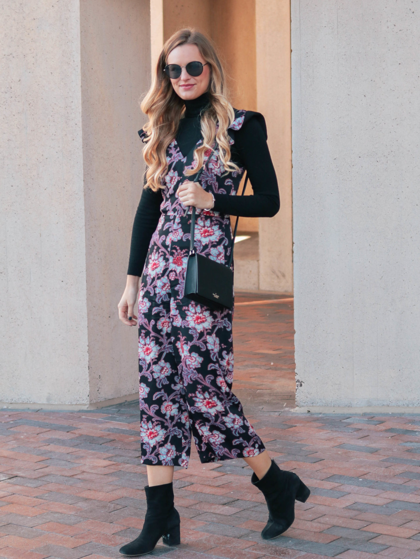Fashion blogger, Leigha Gardner, of The Lilac Press wearing donning a black turtleneck to transition a floral jumper from warm weather wear to winter wear.