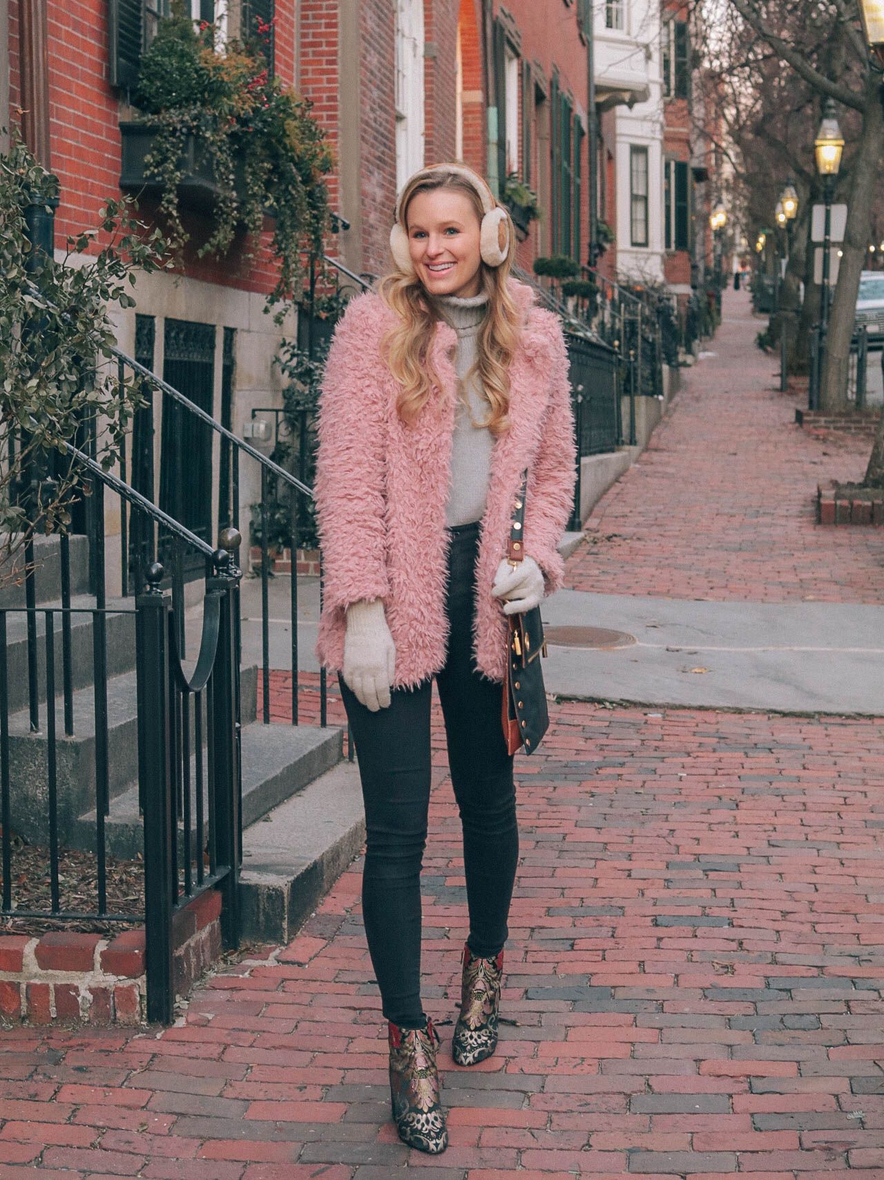Leigha Gardner, of The Lilac Press, making the most of January in Boston with a pink faux fur coat, embroidered booties and sheepskin earmuffs.